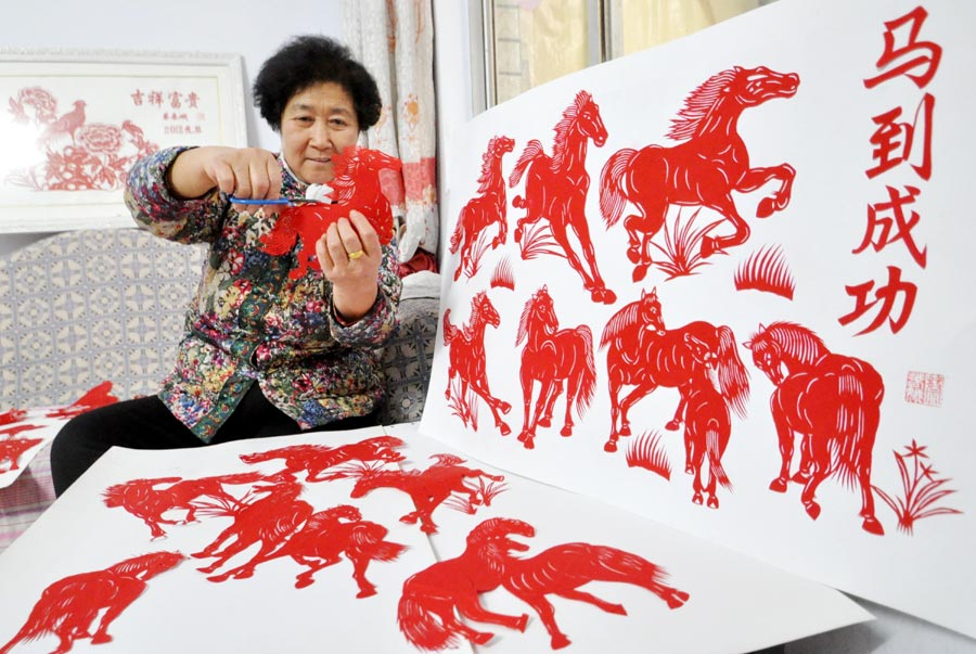 Cai Chun'e, a 68-year-old paper cut artist from Handan, Hebei province, shows her work with the horse theme on December 23, 2013. credit:ECNS.cn