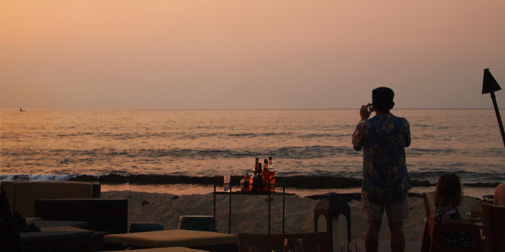 Guests enjoying whale on sunset horizon at ULU Ocean Grill at Four Seasons Resort Hualālai.
